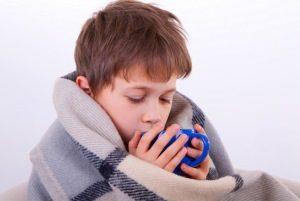 мальчик пьёт, укутавшись в одеяло