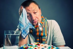 больной гриппом мужчина с градусником во рту