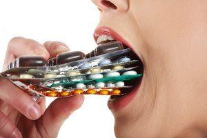 женщина засовывает в рот упаковки таблеток