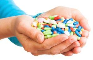 человек держит в руках кучу витаминов