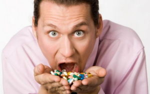 мужчина ест горсть таблеток