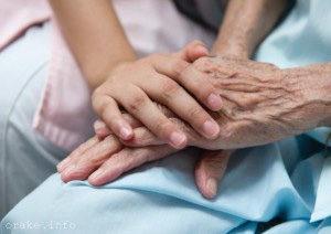 руки молодого человека лежат на руках больного