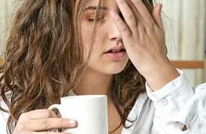 девушка пьёт кофе и держится за голову