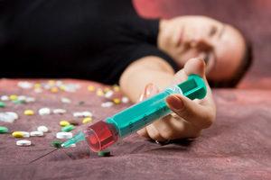 шприц в руке отключившегося наркомана