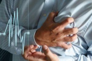мужчина держится руками за сердце на фоне кардиограммы