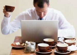 мужчина работает за компьютером в окружении чашек кофе