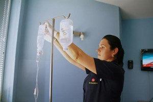 медсестра ставит капельницу для внутривенного вливания растворов