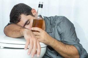 пьяный мужчина держит бутылку и обнимает унитаз