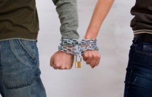 руки, скованные цепями, символизирующие зависимость