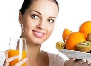 девушка держит в руках фрукты и стакан сока