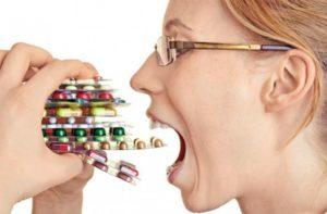 женщина суёт себе в рот пачки таблеток