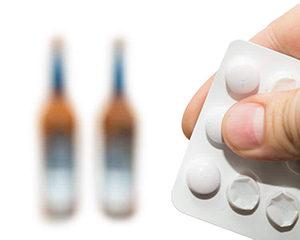 таблетки на фоне бутылок с алкоголем