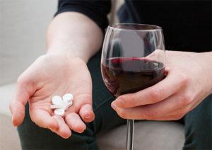 у мужчины в одной руке таблетки, а в другой бокал вина