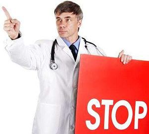 врач со знаком stop в руке