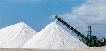 экскаватор насыпает горы соли при её добыче