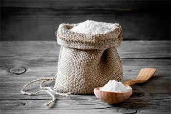 поваренная соль в мешочке и рядом в деревянной ложке